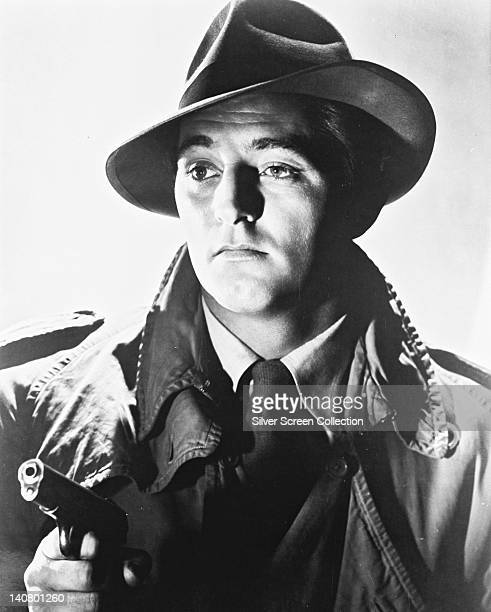 Robert Mitchum US actor in costume and brandishing a handgun in a publicity portrait issued for the film 'The Big Steal' 1949 The Film Noir directed...