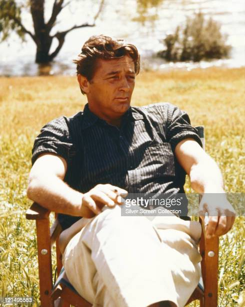 Robert Mitchum US actor sitting in a chair in a field wearing a dark blue shirt with the sleeves rolled up and white trousers smoking a cigarette...