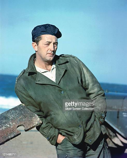 Robert Mitchum US actor wearing a green jacket and a dark blue beret with his hands in the pockets of his trousers leaning a length of rusted metal...