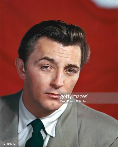 Robert Mitchum US actor wearing a grey jacket a white shirt with a dark green tie in a studio portrait against a red background circa 1950