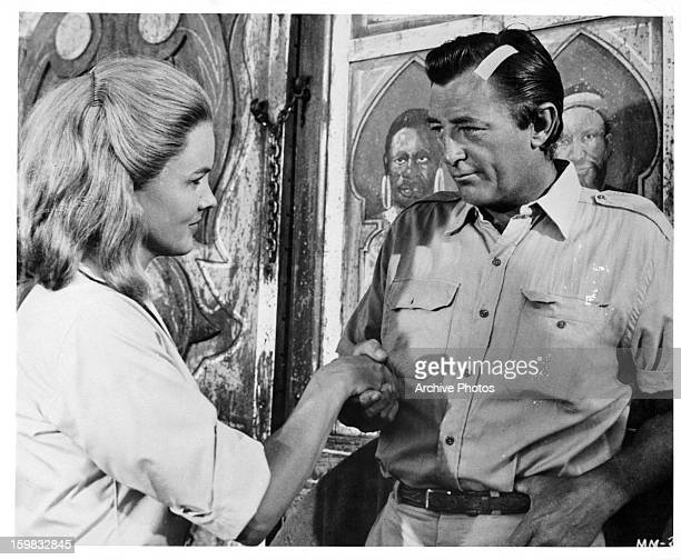 Robert Mitchum with a bandage on his head and holding Carroll Baker hand in a scene from the film 'Mister Moses' 1965