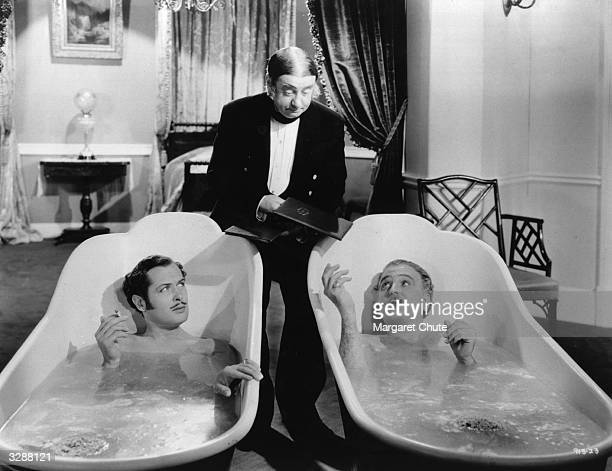 Robert Montgomery and Frank Morgan are handed menus by their butler whilst reclining in hip baths in a scene from the film 'Suicide Club' directed by...
