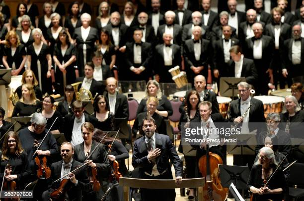 Robert Moody center conductor of the Portland Symphony Orchestra acknowledges the crowd as they give him a standing ovation before he performs his...