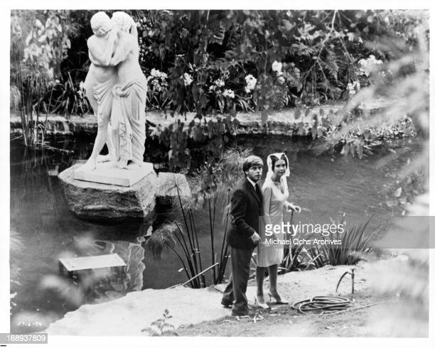 Robert Morse is led by Anjanette Comer into a garden in a scene from the film 'The Loved One' 1965