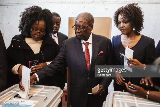 Robert Mugabe former president of Zimbabwe center casts his vote in the ballot box flanked by his daughter Bona Mugabe left and his wife Grace Mugabe...