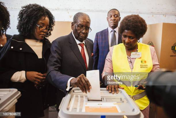 Robert Mugabe former president of Zimbabwe center casts his vote in the ballot box alongside his daughter Bona Mugabe left at a polling station in...