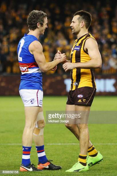 Robert Murphy of the Bulldogs and Luke Hodge of the Hawks shake hands after their retirement match during round 23 AFL match between the Hawthorn...