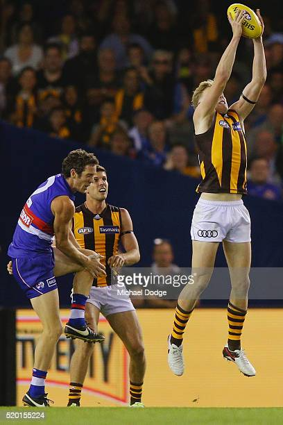 Robert Murphy of the Bulldogs grabs his left knee after sustaining a leg injury as James Sicily of the Hawks marks the ball in the dying stages to...