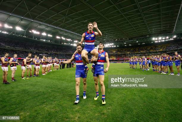 Robert Murphy of the Bulldogs is chaired off after his 300th game by Matthew Boyd and Easton Wood of the Bulldogs during the 2017 AFL round 05 match...