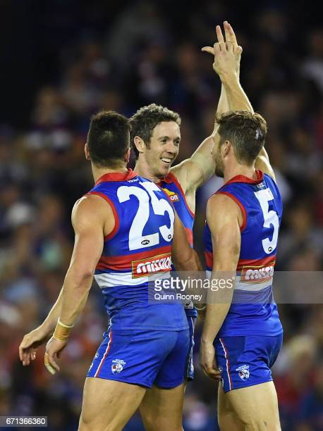 Robert Murphy of the Bulldogs is congratulated by Marcus Adams and Matthew Boyd after winning in his 300th game during the round five AFL match...