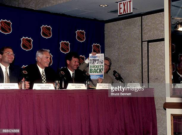 Robert O Naegele Jr owner of the Minnesota Wild holds a newspaper that shows hockey will be back in Minnesota in the year 2000 as Craig L Leipold...