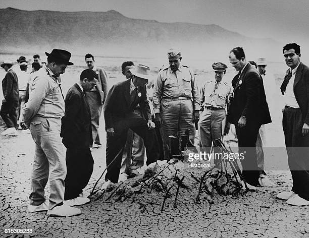 Robert Oppenheimer and General Leslie Groves examine the twisted wreckage that is all that remains of a hundredfoot tower winch and shack that held...