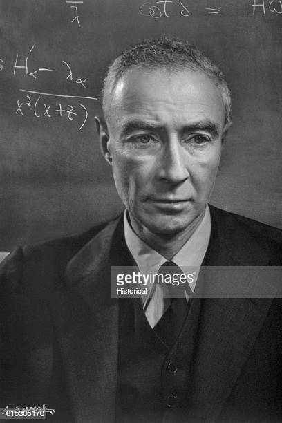 J Robert Oppenheimer stands in front of a blackboard containing algebraic equations