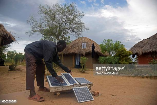 Robert Otala of Alaki Village in Soroti District about 300 kilometres northeast of the capital Kampala is seen checking on his solar panels that he...