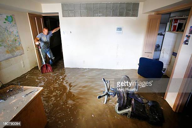 Robert Pandolfi of Longmont Colorado pauses for a moment while using a shovel to direct water in the basement of his boss' home as residents clean up...