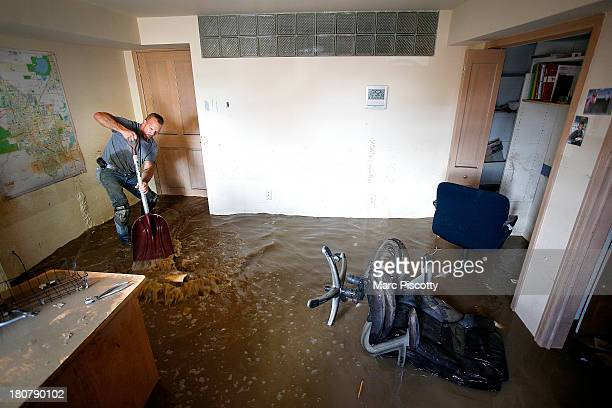 Robert Pandolfi of Longmont Colorado uses a shovel to direct water in the basement of his boss' home as residents clean up in the wake of a week of...