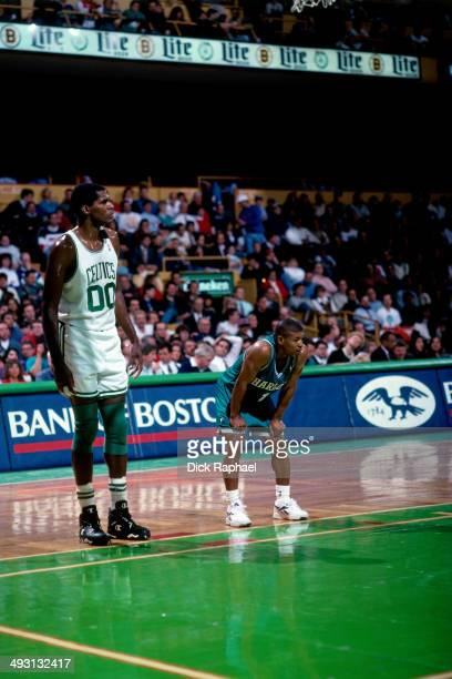 Robert Parish of the Boston Celtics and Muggsy Bogues of the Charlotte Hornets await a free throw during a game played circa 1994 at the Boston...