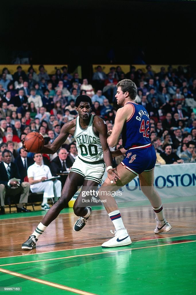 Robert Parish #00 of the Boston Celtics drives to the basket against Mike Gminski #42 of the New Jersey Nets during a game played in 1983 at the Boston Garden in Boston, Massachusetts.