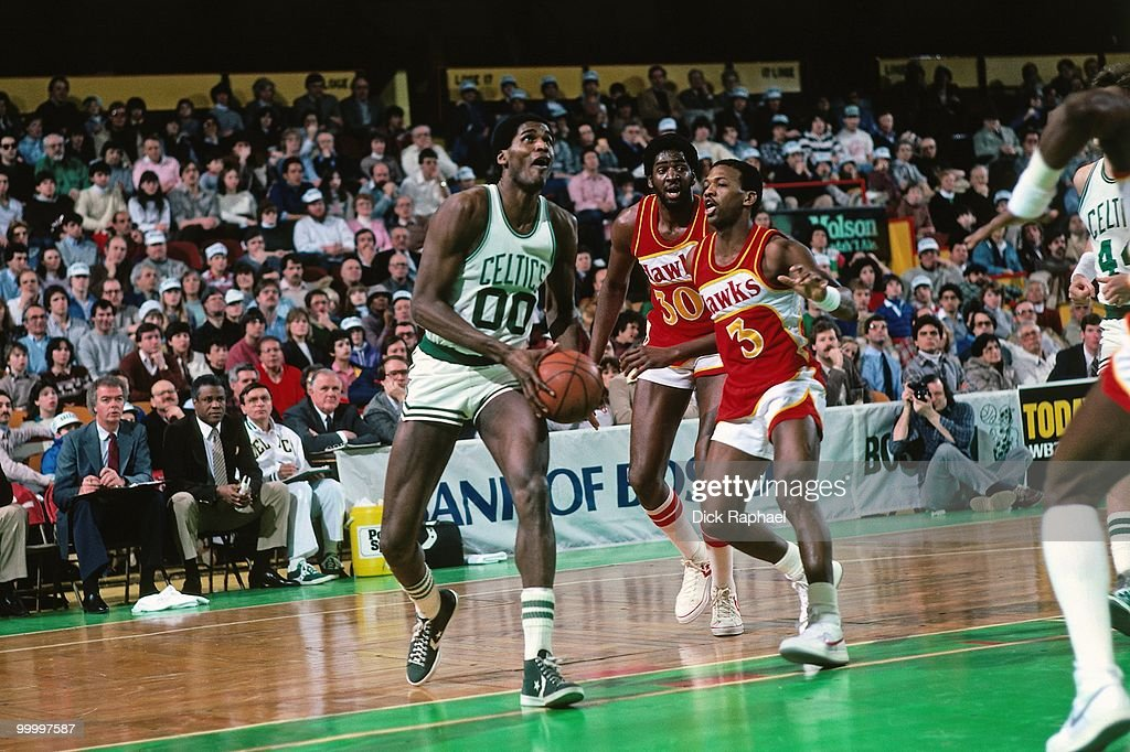 Robert Parish #00 of the Boston Celtics drives to the basket against Eddie Johnson #3 and Tree Rollins #30 of the Atlanta Hawks during a game played in 1983 at the Boston Garden in Boston, Massachusetts.