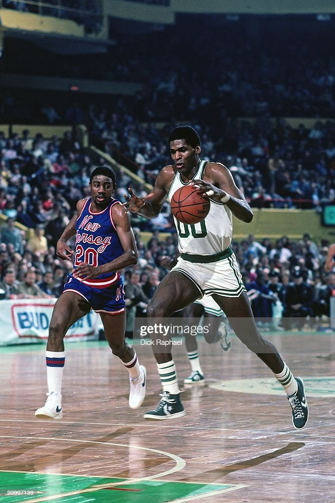 Robert Parish #00 of the Boston Celtics drives to the basket against Micheal Ray Richardson #20 of the New Jersey Nets during a game played in 1983 at the Boston Garden in Boston, Massachusetts.