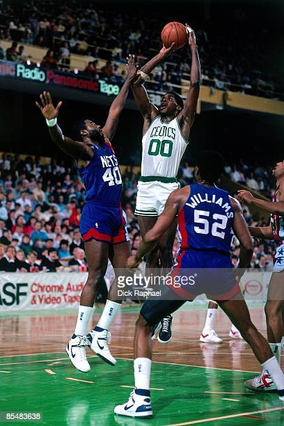 Robert Parish of the Boston Celtics goes up for a shot against Ben Coleman and Buck Williams of the New Jersey Nets during a game played in 1987 at...