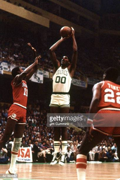 Robert Parish of the Boston Celtics shoots a jump shot against the Philadelphia 76ers during an NBA game in 1980 at the Boston Garden in Boston...