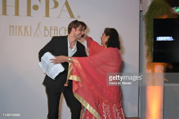 Robert Pattinson and HFPA President Meher Tatna at Nikki Beach for the HFPA Participant Media event honoring Help Refugees on May 19 2019 in Cannes...