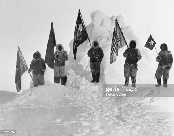 Robert Peary's fellow discoverers dressed in furs and holding flags at the North Pole LR Ooqueah holds the Navy League flag Ootah holds the Delta...