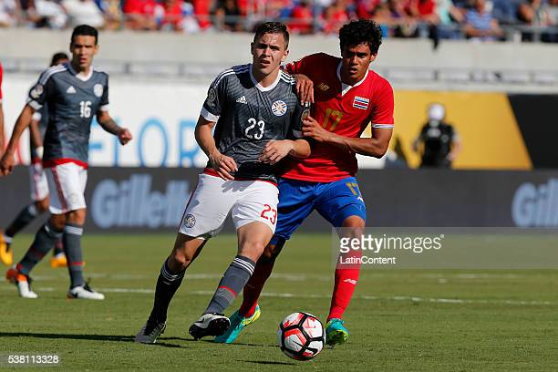 Robert Piris Da Motta of Paraguay passes the ball against Yeltsin Tejeda of Costa Rica during a group A match between Costa Rica and Paraguay at...
