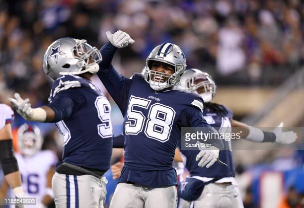 Robert Quinn of the Dallas Cowboys reacts with teammates Demarcus Lawrence and Jaylon Smith after Lawrence sacks Daniel Jones of the New York Giants...