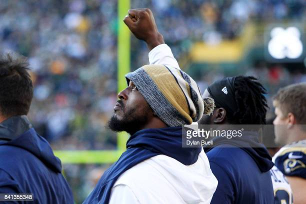 Robert Quinn of the Los Angeles Rams raises his arm during the singing of the national anthem before the game against the Green Bay Packers during a...