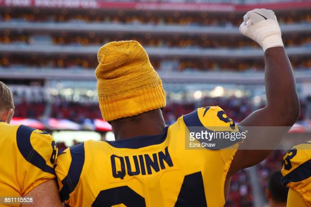 Robert Quinn of the Los Angeles Rams raises his fist during the national anthem prior to their NFL game against the San Francisco 49ers at Levi's...
