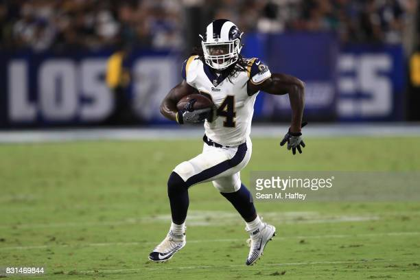 Robert Quinn of the Los Angeles Rams runs with the ball uring the first half of a preseason game against the Dallas Cowboys at Los Angeles Memorial...