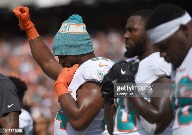 Robert Quinn of the Miami Dolphins raises his first during the playing of the national anthem prior to the start of the game against the Cincinnati...