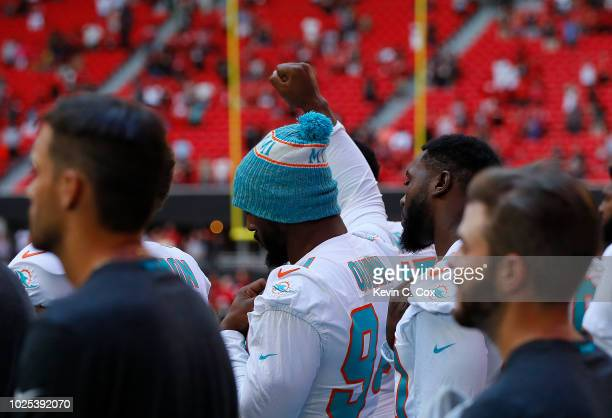 Robert Quinn of the Miami Dolphins raises his fist during the National Anthem prior to the game against the Atlanta Falcons at MercedesBenz Stadium...