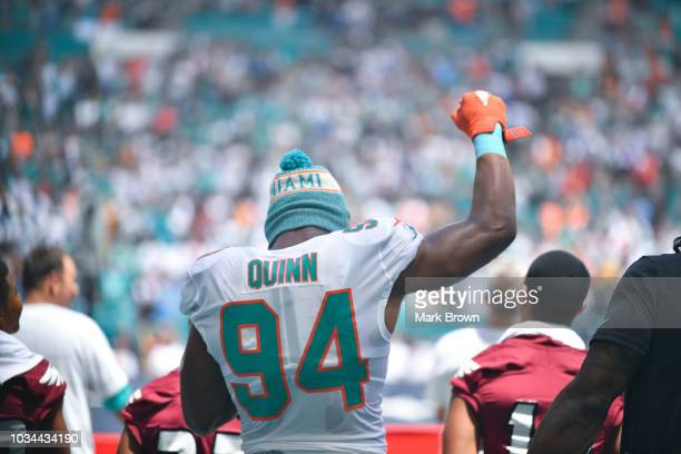 Robert Quinn of the Miami Dolphins raises his fist in the air duding the National Anthem before the game against the Tennessee Titans at Hard Rock...