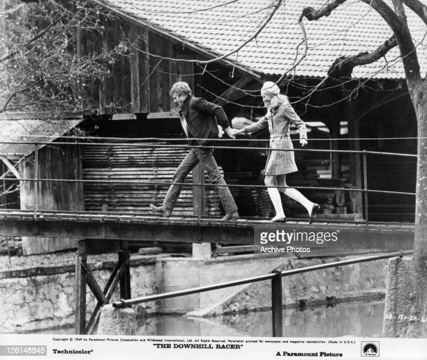 Robert Redford and Camilla Sparv are running across a bridge while holding hands in a scene from the film 'The Downhill Racer' 1969