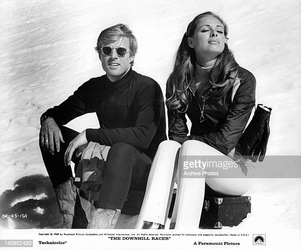 Robert Redford and Camilla Sparv sitting on snow covered slope in a scene from the film 'Downhill Racer' 1969