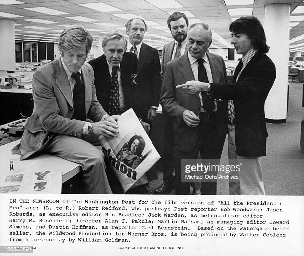 Robert Redford and other actors talk in office in a scene from the film 'All The President's Men', 1976.