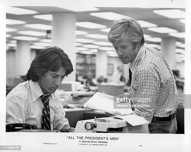 Robert Redford holding papers while speaking to Dustin Hoffman typing on a typewriter in a scene from the film 'All the President's Men' 1976