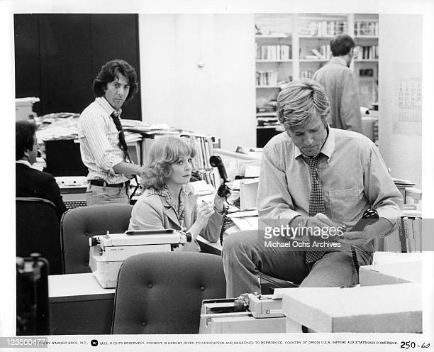 Robert Redford sits on desk in office in a scene from the film 'All The President's Men', 1976.