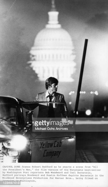 Robert Redford stands behind cab door in a scene from the film 'All The President's Men', 1976.