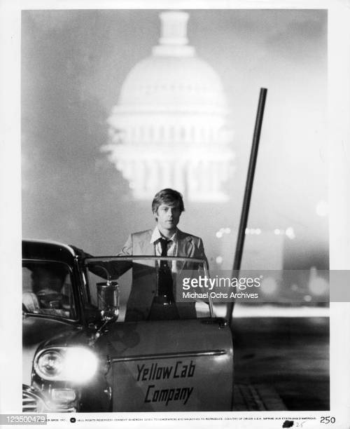 Robert Redford stands behind cab door in a scene from the film 'All The President's Men' 1976