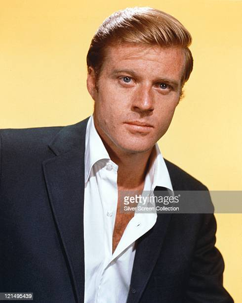 Robert Redford US actor wearing a dark blue jacket with an opennecked white shirt in a studio portrait against a yellow background circa 1965