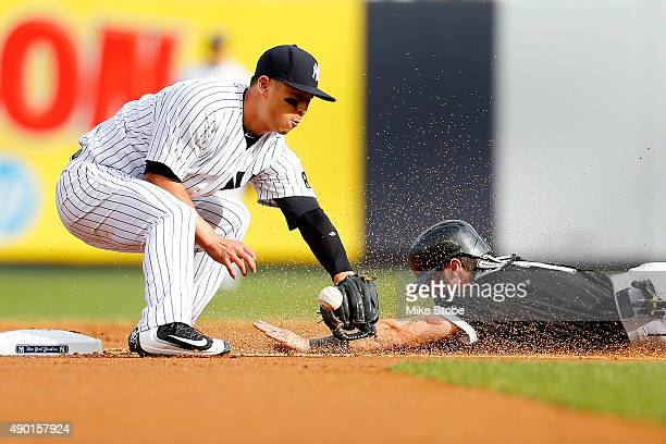 Robert Refsnyder of the New York Yankees is unable to handle the throw as Adam Eaton of the Chicago White Sox steals second base in the first inning...