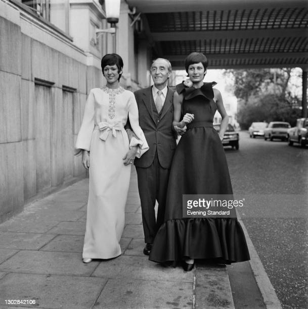 Robert Ricci , who founded the fashion house Nina Ricci with his mother, couturier Maria 'Nina' Ricci, with two models in evening wear, UK, 5th...