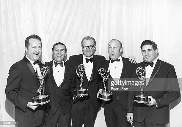 Robert Riger Chet Forte Roone Arledge Charles Fox and an unidentified person pose with Emmy Awards for ABC TV's Wide World of Sports circa 1970