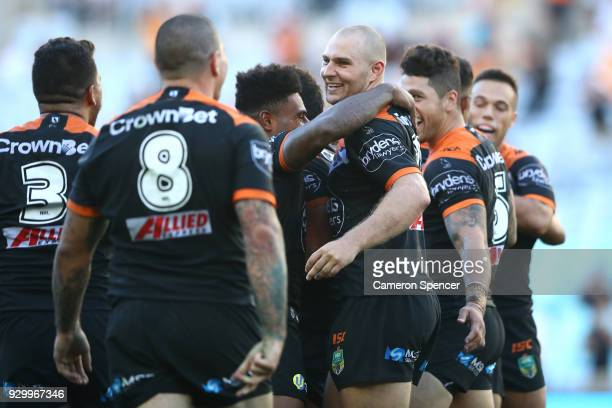 Robert Rochow of the Tigers celebrates with team mates after winning the round one NRL match between the Wests Tigers and the Sydney Roosters at ANZ...