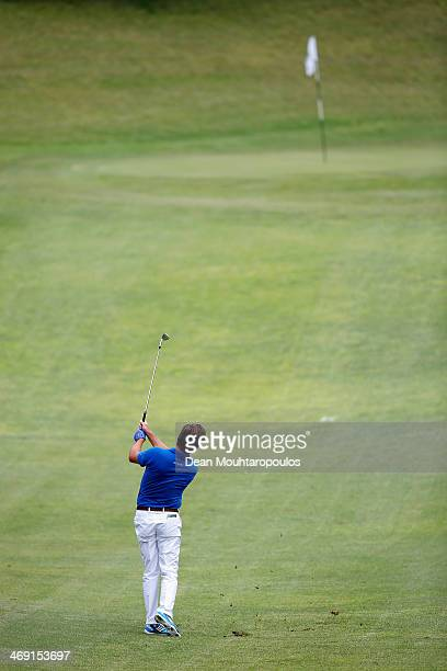 Robert Rock of England hits and sinks his third shot on the 9th hole during Day 1 of the Africa Open at East London Golf Club on February 13 2014 in...