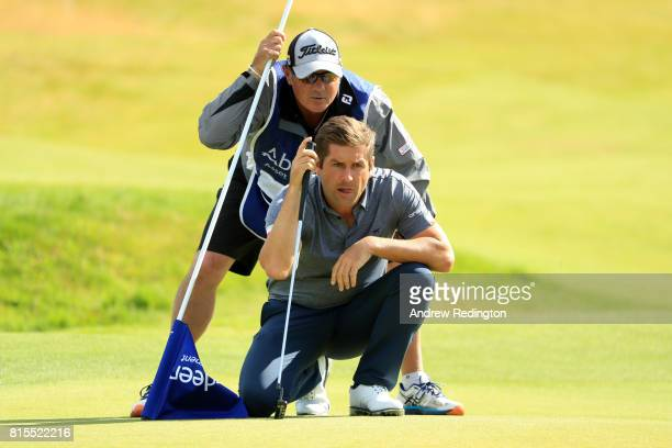 Robert Rock of England lines up a putt on the 18th green with caddie Kyle Roadley during the final round of the AAM Scottish Open at Dundonald Links...